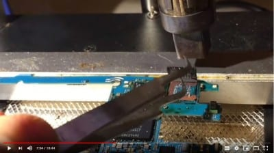 Image of FlashFixers' data recovery video showing removal of memory chip from mobile phone